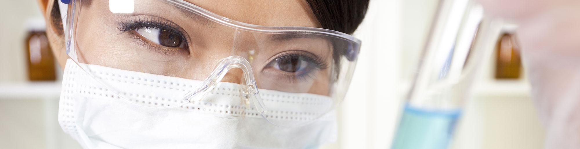 Woman Wearing Safety Glasses and a Medical Mask